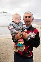 Mongolia, Bayan-Ulgii, Ulgii, Altai Mountains near Tsambagarav Mountain. Man with baby.