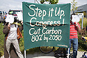 Two protestors with polar bear masks holding a banner spelling 'Step it Up, Congress! Cut Carbon 80% by 2050' in front of a Hummer SUV dealership at a Step It Up 2007 rally. San Rafael, California, USA