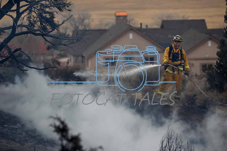 A firefighter puts out hotspots on a 150-200 acre brush fire east of Carson City, Nev., on Friday, Dec. 30, 2011. Initially the fire threatened about two dozen homes before being pushed east by high winds. .Photo by Cathleen Allison