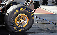 Jan 24, 2009; Chandler, AZ, USA; A detailed view of the Goodyear tire and wheelie bar of an NHRA top fuel dragster as it launches off the starting line during testing at the National Time Trials at Firebird International Raceway. Mandatory Credit: Mark J. Rebilas-