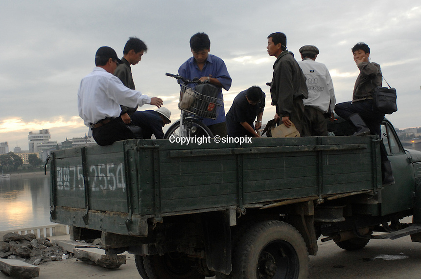 Workers climb aboard a lorry for a lift home at the end of the day in Pyongyang, North Korea.