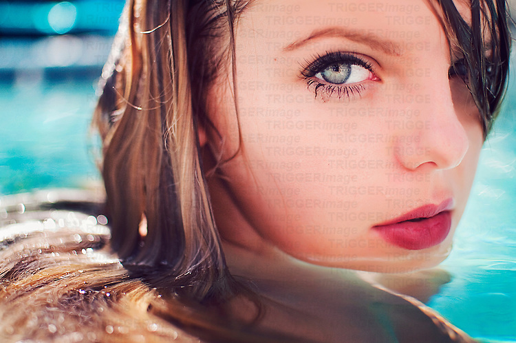 Close up of young woman with wet blonde hair in swimming pool looking at camera