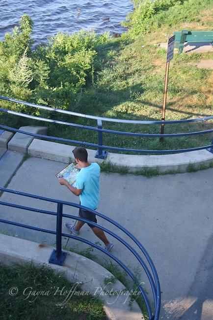 A man walking viewing a map.