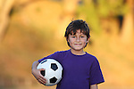 Portrait of young boy with soccer ball at sunset with beautiful gold fall foliage blurred background and copy space to left