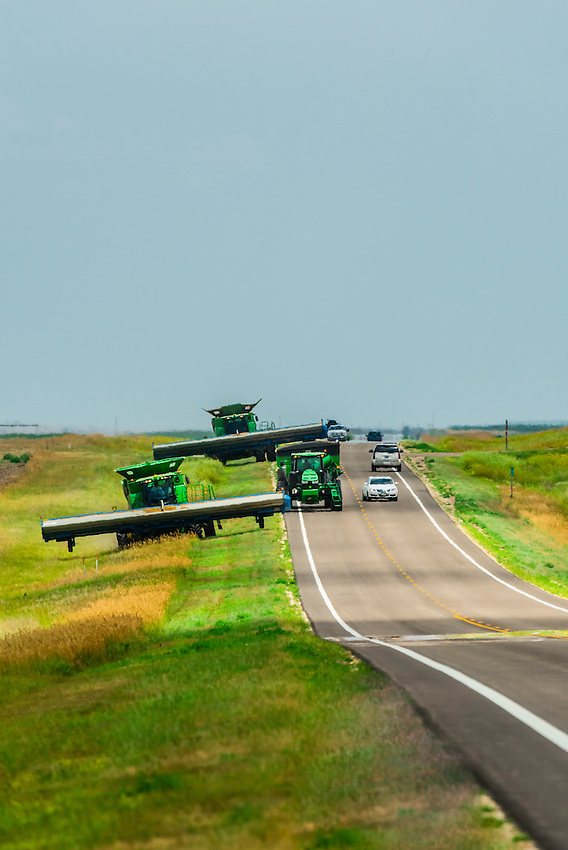 Combine harvesters moving from one field to another during the wheat harvest, along State Highway 27, north of Goodland, Kansas USA.