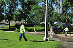 Workers clean debris after powerful storms as others stroll through Lincoln Park and Old Town's expansive lakefront park, also called Lincoln Park, in Chicago, Illinois on June 20, 2009.