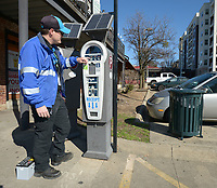 NWA Democrat-Gazette/ANDY SHUPE<br /> Luke Bouxsein, a parking enforcement officer with the city of Fayetteville, changes a battery Friday, March 2, 2018, on a parking pay station off West Avenue in Fayetteville. Consulting firm Nelson/Nygaard has completed a nearly 2-year-long study of parking downtown. On Tuesday, the City Council will discuss implementing the first phase of the study&rsquo;s recommendations. One of the first steps of the recommended downtown parking plan is rebranding parking enforcement officers as customer servers, rather than ticket-writers.