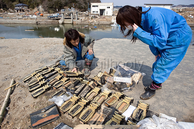 Kenji Onodera (35) and his wife Hiromi (40), look at items salvaged from a temple badly damaged by the March 11 quake and tsunamis in Nobiru, Miyagi Prefecture, Japan on  25 March 20011. Hiromi was nearly swept away by the megatsunami that wrecked the community, in the process losing their 3-month-old daughter, Yume, who she had been holding, but lost due to the force of the wave..Photographer: Robert Gilhooly