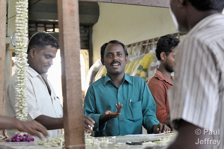 Simon Charles, an educator with the Madras Christian Council of Social Service, talks about HIV and AIDS with workers in the wholesale flower market in Chennai, India.