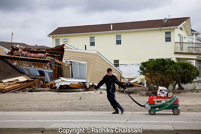 BREEZY POINT-NEW YORK-OCTOBER 31: A young boy recovers possessions from a home in this community devastated by Hurricane Sandy October 31, 2012. Over a 100 homes were lost to fire and many others were damaged by wind and flooding.