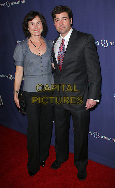 "KATHRYN & KYLE CHANDLER.The Alzheimer's Association's 17th Annual ""A Night At Sardi's"" held at the Beverly Hilton Hotel, Beverly Hills, California, USA..March 4th, 2009.full length grey gray jacket black trousers suit married husband wife.CAP/ADM/KB.©Kevan Brooks/AdMedia/Capital Pictures."