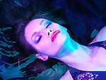 Beauty treatment conceptual photo. Woman lying in water wearing makeup under colored light. Closeup of face.
