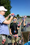 "Trent Kettles of Lynden places a festive hat on one of his sons while telling his other son to not cover his face with the flag. ""We don't cover our faces,"" Kettles said. ""Only cowards cover their faces."" Photo by Daniel Berman/www.bermanphotos.com"
