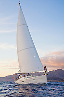Woman on bow of cruising sailboat off the west coast of Oahu, Hawaii, with Waianae Mountain Range in the background