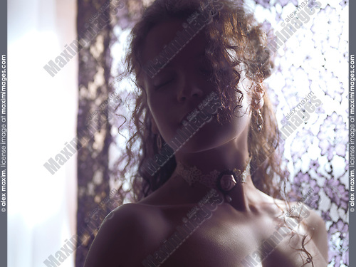 Sensual beauty portrait of a young woman wearing a choker with a rose standing by the window curtain lit by soft sunlight