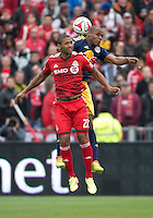 Toronto, Ontario - May 17, 2014: New York Red Bulls defender Jamison Olave #4 jumps for a ball with Toronto FC forward Luke Moore #27 during a game between the New York Red Bulls and Toronto FC at BMO Field. Toronto FC won 2-0.