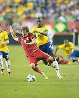 Portugal defender Fabio Coentrao (5) reacts to being tackled by Brazil midfielder Ramires.  In an International friendly match Brazil defeated Portugal, 3-1, at Gillette Stadium on Sep 10, 2013.
