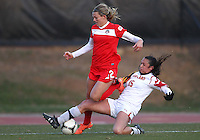 COLLEGE PARK, MARYLAND - April 03, 2013:  Stephanie Ochs (22) of The Washington Spirit is slide tackled by Erika Nelson (15) of the University of Maryland women's soccer team in a NWSL (National Women's Soccer League) pre season exhibition game at Ludwig Field in College Park Maryland on April 03. Maryland won 2-0.