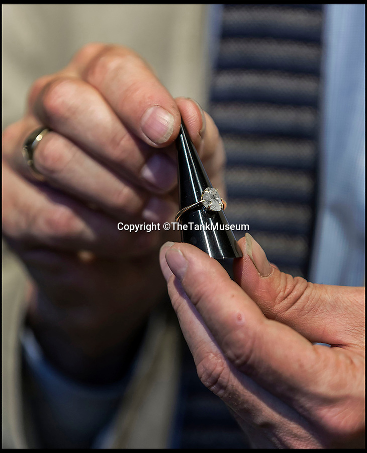 BNPS.co.uk (01202 558833)<br /> Pic: TheTankMuseum/BNPS<br /> <br /> David Willey the curator of Bovington tank Museum in Dorset with the ring.<br /> <br /> A poignant ring made from a shard of glass that struck a First World War tank commander when his periscope took a direct hit has been unearthed 100 years later.<br /> <br /> Lieutenant Sir Basil Henriques was peering into the viewpoint during the first outing of the Mk I tank on the battlefield when artillery fire struck a glass prism that shattered, sending splinters into his face.<br /> <br /> Medics later removed the pieces and the officer kept the largest part and had it mounted in a gold ring which he then gave to his new bride, Rose. The item has been unearthed in the archives of the Tank Museum in Dorset.