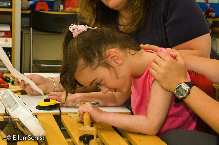 MR / New York, NY. Standing Tall: An educational program for students with neuromotor disablilities that uses the principals of conductive education, which combines a structured intensive program of daily physical training with traditional academic studies. ID: AI-gSst. Girl (6; Cerebral Palsy) in conductive education classroom presses yellow switch (a scanning device (AAC) during lesson with speech language pathologist. MR: Dyc1, Sel4. © Ellen B. Senisi