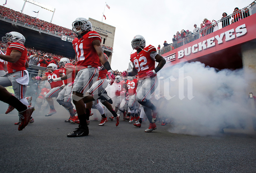 Ohio State Buckeyes defensive back Vonn Bell (11) and defensive lineman Adolphus Washington (92) take the field prior to the NCAA football game against the Rutgers Scarlet Knights at Ohio Stadium in Columbus on Oct. 18, 2014. (Adam Cairns / The Columbus Dispatch)
