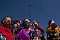 "Ethnic Tibetan people protect themselves from the smell of decomposing body as vultures come from skies during a sky burial near the Larung valley located some 3700 to 4000 metres above the sea level in Sertar county, Garze Tibetan Autonomous Prefecture, Sichuan province, China October 31, 2015. In early afternoons, on a hill near famous Larung Wuming Buddhist Institute relatives and onlookers gather for sky burials in which bodies of deceased people are offered to vultures to prey upon it. Such burials are practiced by some Tibetans and Mongolian in China as an extreme type of Buddhist's ""self-sacrifice almsgiving"". It is believed that feeding vultures with decomposed corpse of relatives on top of a mountain is a respectful to pay tribute to their passed-away beloved ones. Picture taken November 1, 2015.  REUTERS/Damir Sagolj"