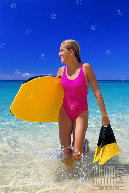Young woman in a bright pink swimsuit carries her bodyboard and fins as she approaches the shore at a beautiful beach on Oahu.