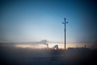 Refinery towers stand above trees outside Ufa, Bashkortostan, Russia. The area is a major oil and gas producing region in the country.