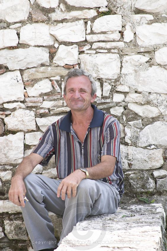 A man sitting in the shade by a white wall with a big happy smile on his face. Berat upper citadel old walled city. Albania, Balkan, Europe.