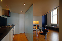 The dining area is separated from the kitchen by a glass panel