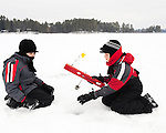 Two young brothers enjoy fishing for northern pike on a frozen lake.