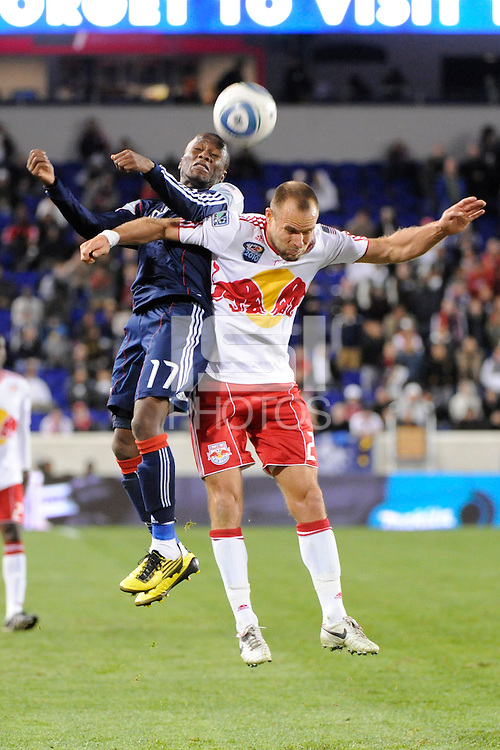 Sainey Nyassi (17) of the New England Revolution and Joel Lindpere (20) of the New York Red Bulls go up for a header. The New York Red Bulls defeated the New England Revolution 2-0 during a Major League Soccer (MLS) match at Red Bull Arena in Harrison, NJ, on October 21, 2010.