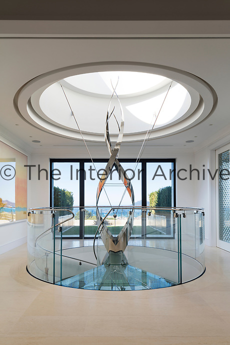 The delicate spiral staircase, designed by Eva Jiricna, rises up through the upper terraces into a domed skylight.