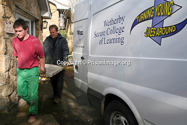 Ben, a young offender carrying a paving stone with Geoff, the course instructor from the Inside Out Trust. Wetherby Young Offenders Secure College of Learning. Yorkshire, UK. It is part of Ben's education to perform manual tasks for residents in the community local to his prison.