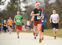 NWA Media/ANDY SHUPE - Alana Uriell, a University of Arkansas freshman and member of the university's golf team from Carlsbad, Calif., runs during the Jingle Bell Run/Walk for Arthritis Sunday, Dec. 14, 2014, at Lake Fayetteville Park in Fayetteville. The event featured a 5-kilometer run, a 1-mile walk and a tot-trot for children to support the Arthritis Foundation.