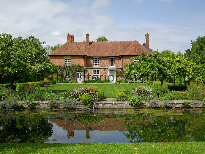 The canal demarcates the end of the lawn of this manor house which has been converted into a contemporary ecological family home