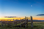 Teton County, Montana: Cattle pen under a quarter moon at dawn along the Front Range