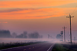 Two lane rural country road and radiation fog and glowing orange clouds at sunrise, Merced, Central Valley, California