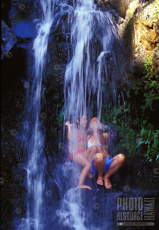 Mother and daughter playing in waterfall