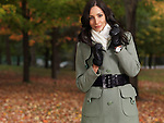 Beautiful smiling woman wearing a green coat walking through a park in fall