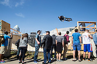 Top professional BMX riders showcase their talents and catch air on a BMX half pipe ramp at SXSW Music Festival in downtown Austin, Texas.