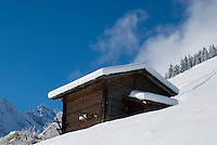 Mountain Barn on snow covered slopes of Gimmelwald in Swiss Alps