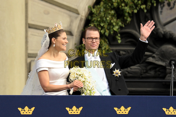 CROWN PRINCESS VICTORIA OF SWEDEN, DUCHESS OF VASTERGOTLAND, PRINCE DANIEL, DUKE OF VASTERGOTLAND OF SWEDEN.Wedding Of Swedish Crown Princess Victoria and Daniel Westling, Princess Couple at Lejonbacken Terrace at the Royal Palace, Stockholm, Sweden,.19th June 2010.half length gold crown veil hand waving glasses bouquet flowers bow tie tuxedo tux  white dress bride groom.CAP/RD .©Richard Dean/Capital Pictures