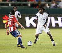 Revolution midfielder Sharlie Joseph (21) moves past Chivas midfielder Paulo Nagamura during the first half of the game between Chivas USA and the New England Revolution at the Home Depot Center in Carson, CA, on September 10, 2010. Chivas USA 2, New England Revolution 0.