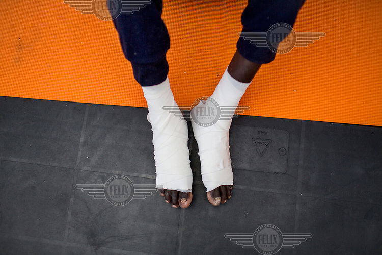 A man from Sudan sits with his bandaged feet safely on board the Bourbon Argos after a long perilous journey during which he has suffered serious violence. He told an MSF (Medicins Sans Frontiere) cultural mediator that his feet were severely injured because one week ago he was repeatably beaten with an iron bar. In total, that day, MSF took on board 169 people in the Mediterranean sea, around 25 nautical miles from Libya.