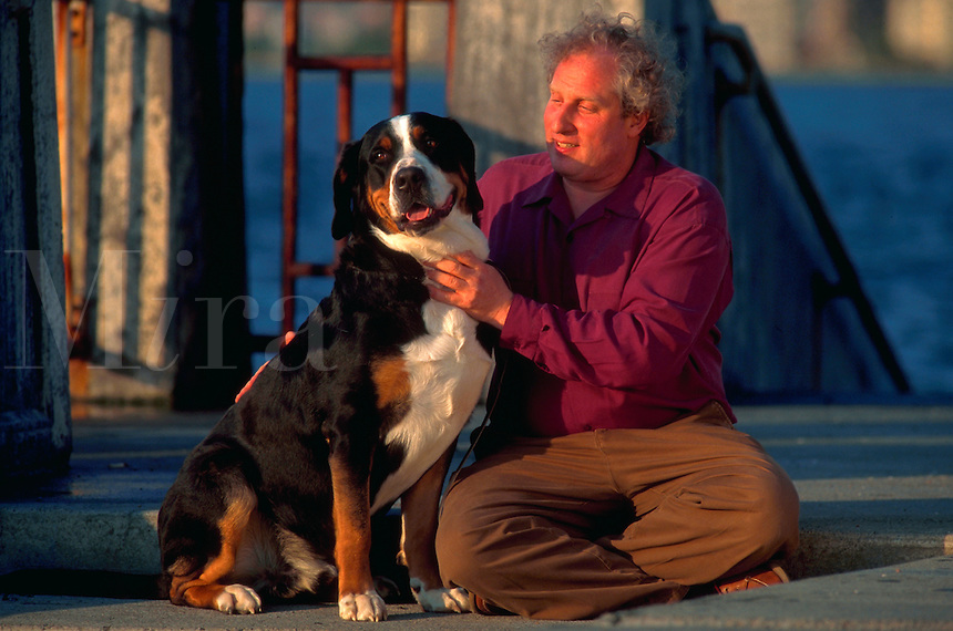 Man sits with his greater swiss mountain dog.