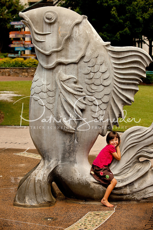 A young girl plays on the Fish Fountain, one of many public art pieces in The Green in downtown Charlotte. The Green, located at 435 South Tryon St., is a popular urban park in the heart of Charlotte, NC.