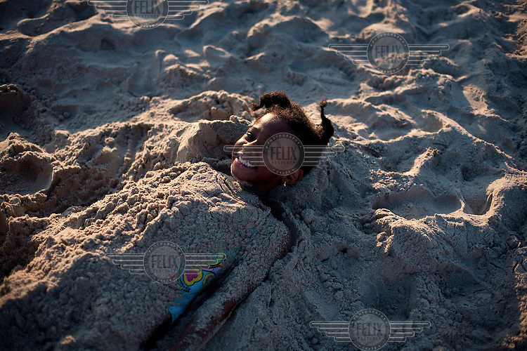 A girl lies half sunk in the sand on Rockaway Beach, New York. Made famous by the classic song by The Ramones, it stretches for miles along the Atlantic Ocean, while still staying within the borders of New York City.