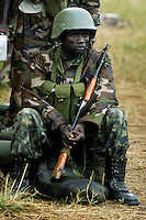 Cradling his Kalashnikov AK-47, a UPDF soldier awaits a deployment assignemnts after arriving with the president's convoy at an army camp near Akwang north of Lira while coleagues hunt for the LRA commander responsable for attacking the Barlonyo IDP camp Saturday, Feb 21, 2004. (Rick D'Elia)