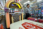 Yuki Maezuki, who runs a bar in the Roppongi entertainments district, walks past a Wurlitzer duke box on sale for ¥1.6 million (U.S.$19,709) at Shimura Seisakusho, a shop specializing in retro American diner goods, in the Kappabashi district of Tokyo, Japan on Nov. 10 2010. Often called Tokyo's Kitchen Town, stores in Kappabashi still mainly caters to professionals in the catering industry, though is becoming increasingly popular with foreigners hunting for unique souvenirs..Photographer: Robert Gilhooly